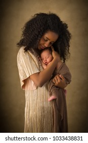 Happy young African mother in shiny gold dress posing with her 7 days old newborn baby
