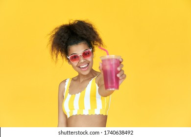 Happy young african teen hipster gen z girl holding drink look at camera wear sunglasses enjoy cool cocktail laughing having fun isolated on yellow party summer studio background. Portrait copy space