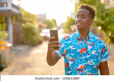Happy young African tourist man using phone outdoors