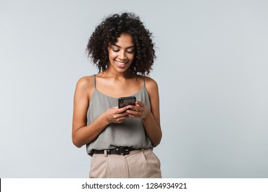 Happy young african woman casually dressed standing isolated over gray background, using mobile phone