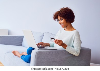Happy young african woman doing online payments with her credit card and laptop