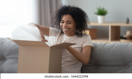 Happy young african woman satisfied customer open parcel cardboard box sit on sofa at home, smiling black girl consumer unpack carton package receive good purchase postal shipping delivery concept