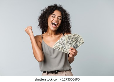 Happy young african woman standing isolated over gray background, holding bunch of money banknotes, celebrating