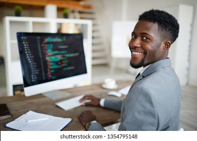 Happy young African-american software developer in formalwear sitting by workplace in front of computer screen with decoded data