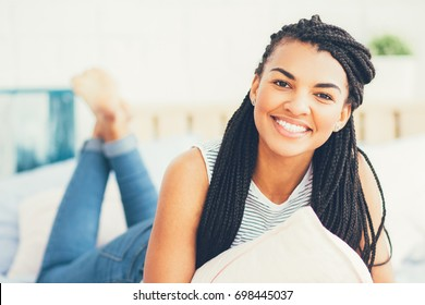 Happy young African-American woman resting in bed
