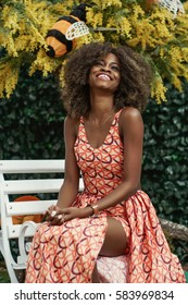 Happy young afro american girl with amazing slin tone wearing long dress and sitting in a shopping mall.