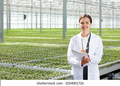 Happy young agro-engineer in whitecoat looking at camera while making working notes