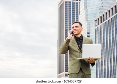 Happy Young American Businessman traveling, working in New York, wearing green suit, standing in front of business district with high buildings, working on laptop computer, calling on cell phone.