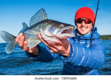 Happy young angler with Zander fish on a natural lake background