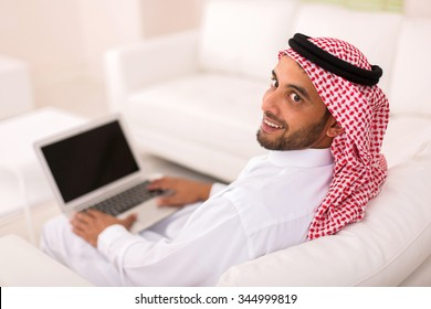 happy young arabian man with laptop looking back