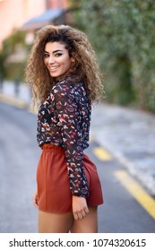Happy young arabic woman with black curly hairstyle. Arab girl smiling in the street moving her hair.