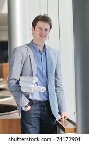 happy young architect business man portrait with paper blueprints plan