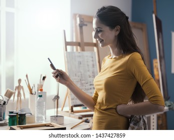 Happy young artist in her art studio, she is standing next to her painting and chatting with her smartphone