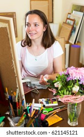 Happy young artist paints a picture at home