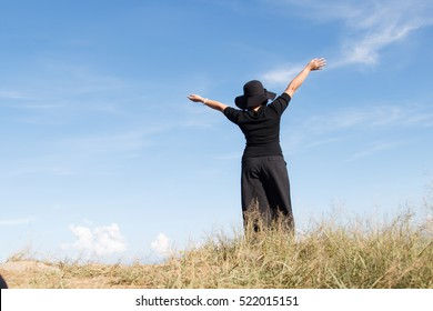 Happy young asia woman enjoying sunny day. black dress of woman standing in meadow,freedom in summer
