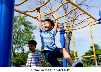 Happy Young asian boy hang the yellow bar by his hand to exercise at out door playground under the strong sunlight in summer time.