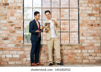 Happy young Asian business people discussing article on digital tablet when drinking take away coffee