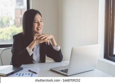 Fröhliche junge asiatische Geschäftsfrau, die bei der Videokonferenz mit ihrem Team den Grußpartner in die Hand winkt.