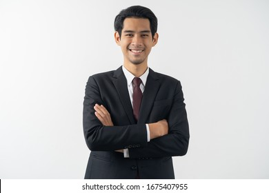 happy young asian businessman smiling and folded arms in formal suit isolated on white background.