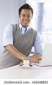 Happy young Asian businessman using laptop computer, smiling, looking at camera, leaning on counter.
