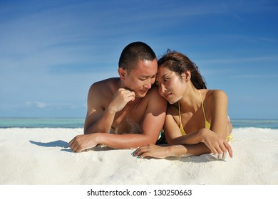 happy young asian couple enjoying summer and have on beautiful white sand beach