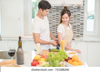Happy young asian couple, husband help his wife to put on apron before cooking in the kitchen at home.