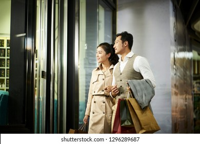 happy young asian couple looking into window of a shop in shopping mall