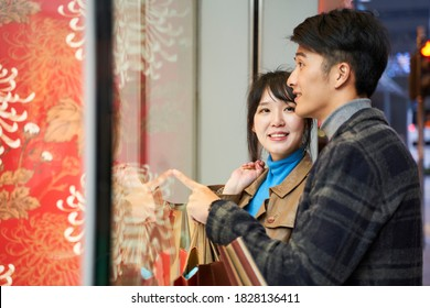 happy young asian couple looking into shop window in modern city