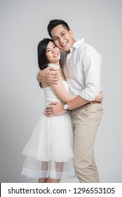 Happy young Asian couple in love embracing on white background