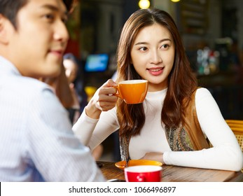 happy young asian couple lovers sitting at table in coffee shop.