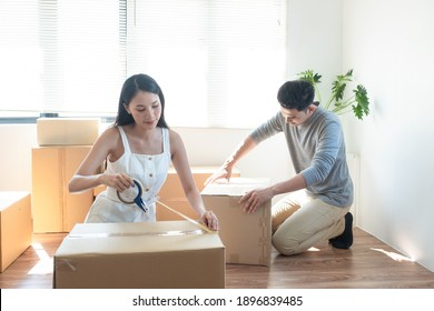 Happy young  Asian couple packing box together for moving to new house. Young couple.