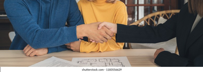 Happy young Asian couple and realtor agent. Cheerful young man signing some documents and handshaking with broker while sitting at desk. Signing good condition contract.  Panoramic banner background.