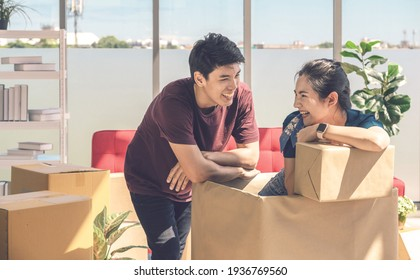 Happy young asian couple smiling relaxing and having fun while playing with cardboard box in new house, celebrating moving to new home concept