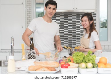 Happy young asian couple teasing and enjoy cooking together in the kitchen at home.