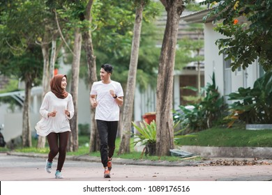 happy young asian couple working on exercise and warm up to jogging and running outdoors