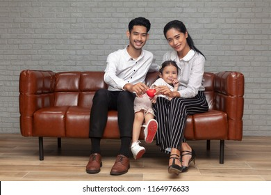 Happy Young Asian family with children relaxing on sofa. concept housing a young family. International Day of Families