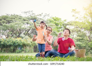 Happy young asian family playing with bubble wands with daughter in park outdoors in summer or spring. Together community love fresh green eco lifestyle family day concept