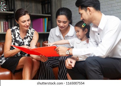 Happy young Asian family talking with psychologist or family counselor In life insurance coverage or real-estate agent house investment or bank worker offers loan or financial advisor with clients.