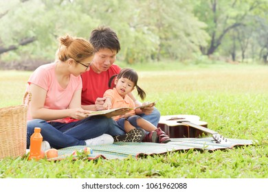 Happy young Asian family with their daughter Reading a book. People having fun in nature at park outdoor.