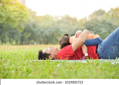 Happy young Asian father and his daughter are hugging together and sleeping on the grass in nature at park outdoor. Family.