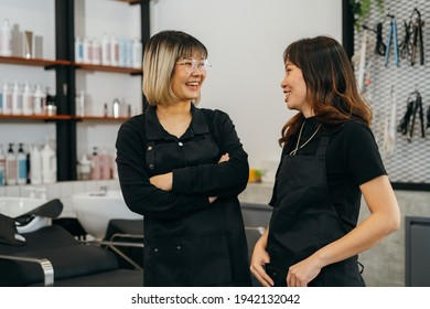 Happy young Asian female hairstylist colleagues working in salon standing wearing apron and spectacles talking to each other