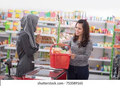 happy young asian female shopkeeper or cashier  welcoming customer at supermarket