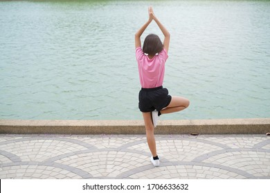 Happy young asian girl doing yoga sport at garden.