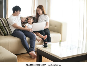 Happy young Asian girl with her lovely parents using laptop computer for education and spent quality time together. Asian family, Social Distancing, homeschooling, work from home or love concept