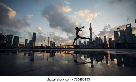 Happy young Asian girl  jumping of success in front of urban sun rise skyline in Shanghai