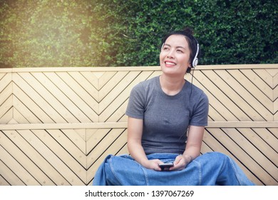 Happy young asian girl listening music with her mobilephone.