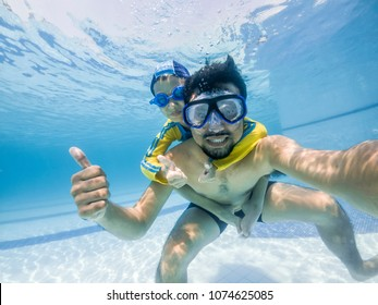 Happy young asian kid and dad with swim goggles underwater, smile relax face swimmer have fun activity