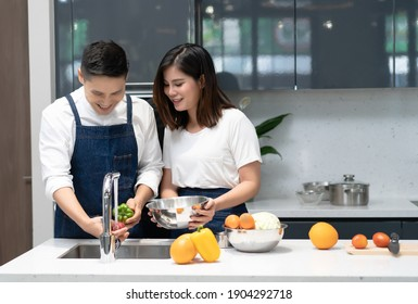Happy young Asian love couple standing in kitchen cooking morning together husband washing vegetables while his wife helped hold a bowl of vegetables. Couple spending time together at home.