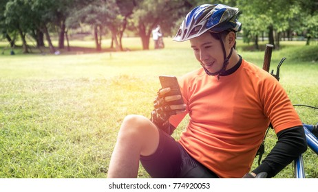 Happy young asian male cyclist in orange sportswear using Mobile Phone In Park, Beautiful sunny day.