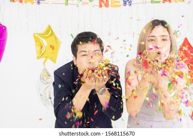Happy young Asian male and female blowing a colorful, shiny glitter, confetti at a New Year party. having fun together. couple in love concept.